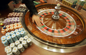 """A staff member demonstrates the roulette wheel for the media at the new casino """"Grand Lisboa Casino"""" in Macau, Sunday, Feb. 11, 2007. Billionaire gambling king Stanley Ho celebrated the long-awaited opening Sunday of his Grand Lisboa casino _ a gleaming gold complex that is Ho's biggest response to American rivals who have stormed into Macau and seized big chunks of the gaming market.  (AP Photo/Kin Cheung) ORG XMIT: XKC132"""